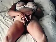 Tanned milf rubbing her clit on her bed